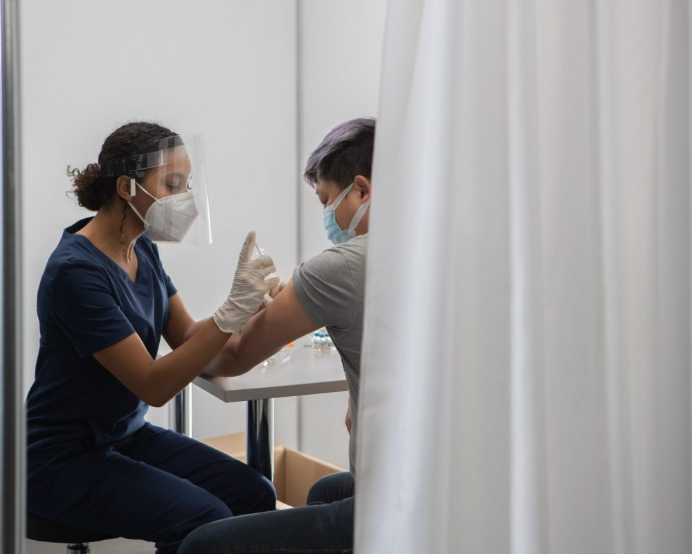 African American female doctor prepares to administer vaccine in a cabin