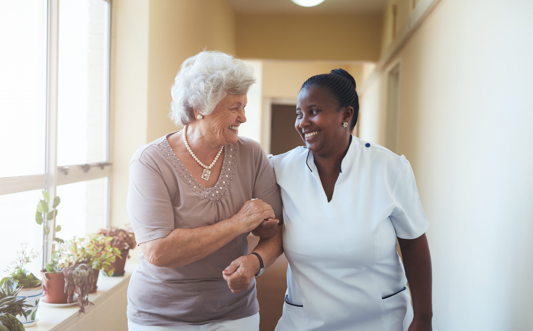 Smiling home caregiver and senior woman walking together through a corridor and holding hands.